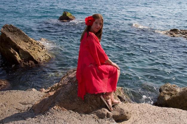 海沿いの緋色のドレスを着た女の子。風、波、人けのないビーチ。南の休日