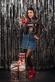 雨の形で銀色の背景にギフトと光沢のあるジャケットとスカートの女の子。