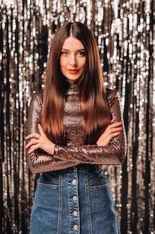 新年の雨の銀色の背景に光沢のあるジャケットを着た女の子。