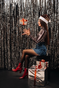 雨の形で銀色の背景に贈り物とサンタの帽子をかぶった光沢のあるジャケットの女の子。