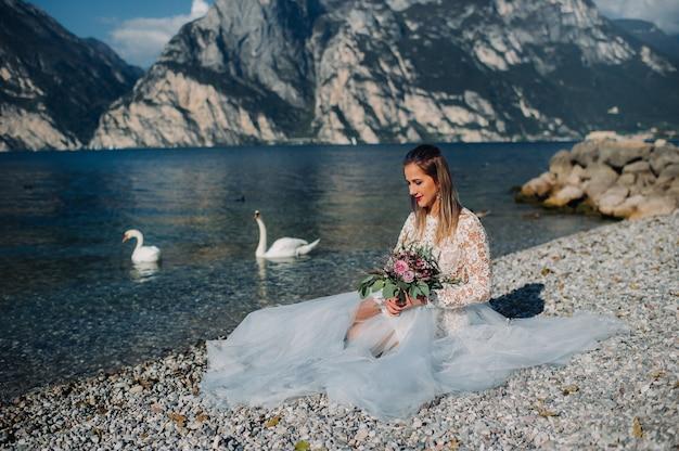 ガルダ湖の堤防にスマートな白いドレスを着た女の子が座っています。イタリアの山と湖を背景に女性が撮影されています。トルボレ。