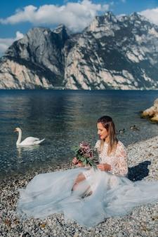 ガルダ湖の堤防にスマートな白いドレスを着た女の子が座っています。イタリアの山と湖を背景に女性が撮影されています。トルボレ