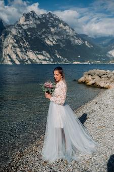 ガルダ湖の堤防をスマートな白いドレスを着た女の子が歩いています。イタリアの山と湖を背景に女性が撮影されています。トルボレ。