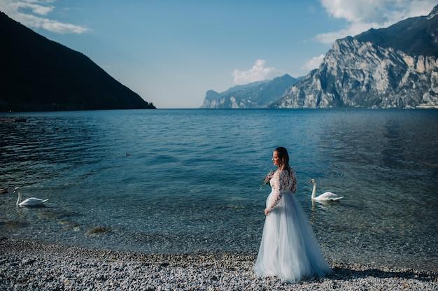 ガルダ湖の堤防を歩くスマートな白いドレスを着た女の子。イタリアの山と湖を背景に女性が撮影されています。トルボレ