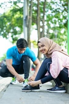 笑顔のベールを着た女の子が、公園で屋外でジョギングする前に靴ひもを修理します