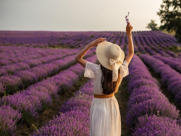 Девушка в соломенной шляпе стоит на лавандовом поле.
