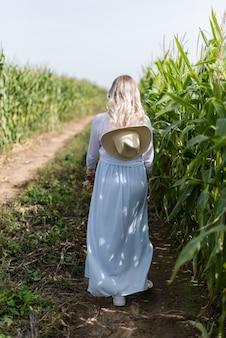 밀짚모자를 쓴 소녀가 옥수수밭을 걷고 있다