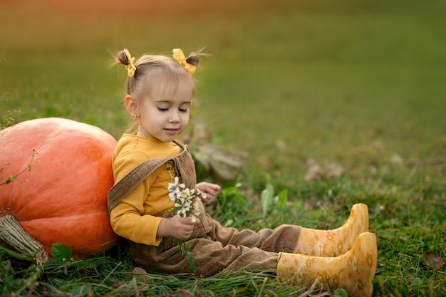 Strucx 점프수트를 입은 소녀가 채소밭의 잔디에 앉아 있다