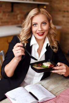 Девушка в костюме обедает и улыбается. доставка еды