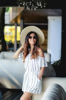 テラスで夏のドレス、帽子、サンダルの女の子。