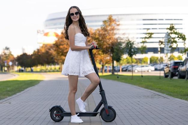 夏のドレスを着た女の子が歩道で電動スクーターに乗る