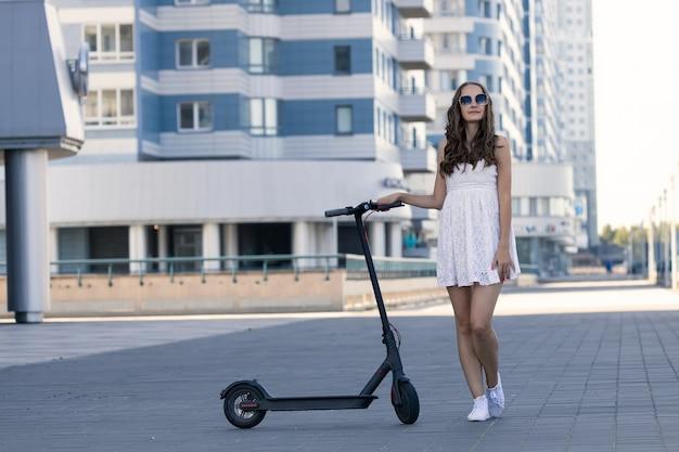 街の電動スクーターの横に立つ夏服の女の子