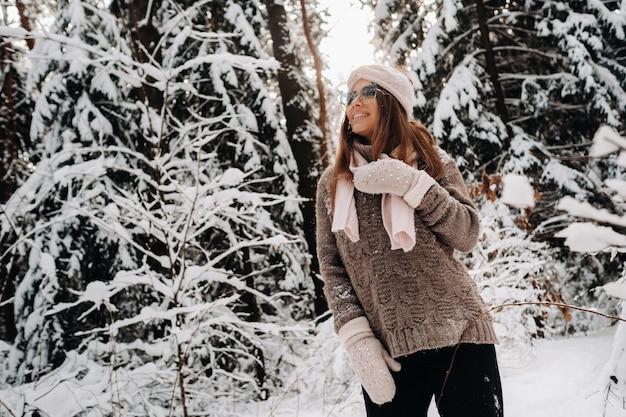 雪に覆われた森で冬にセーターとメガネの女の子