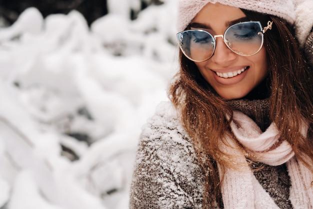 雪に覆われた森の冬のセーターとメガネの女の子。