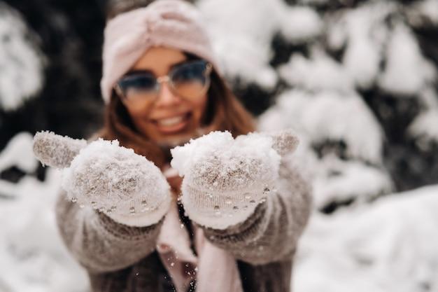 雪に覆われた森の冬のセーターとメガネの女の子