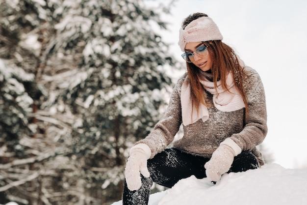 冬のセーターとメガネの女の子は、森の雪に覆われた背景に座っています
