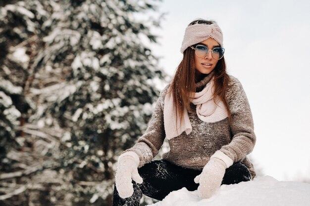 冬のセーターとメガネの女の子は、森の雪に覆われた背景に座っています。