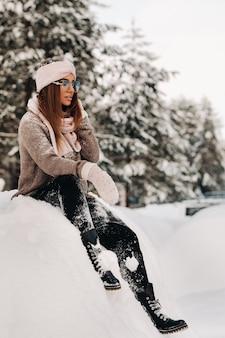 Девушка в свитере и очках зимой сидит на заснеженном фоне в лесу.
