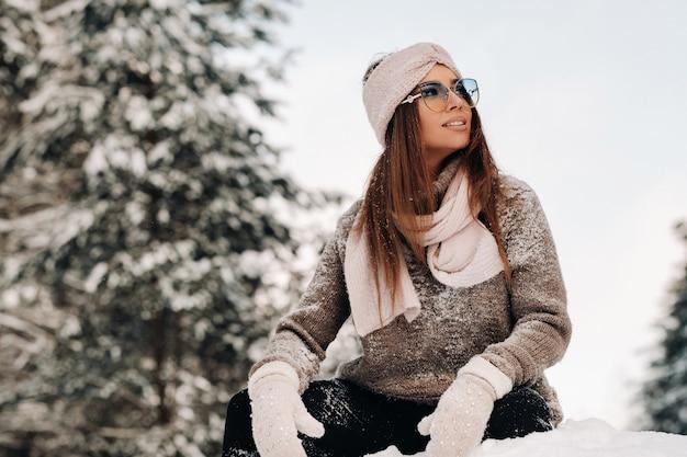 冬のセーターとメガネの女の子は雪に覆われた上に座っています
