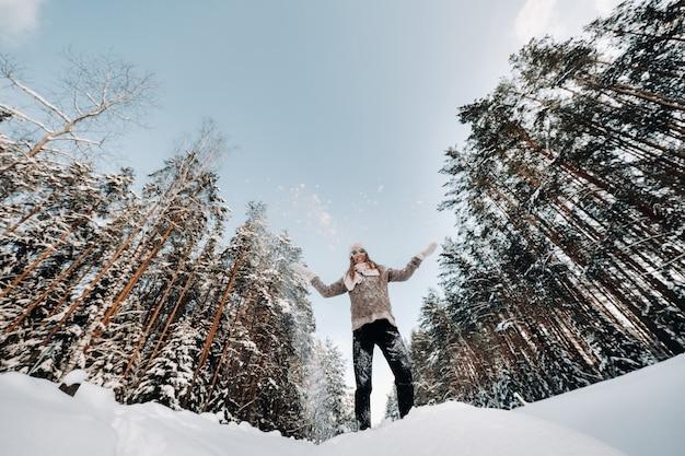 冬のセーターとミトンの女の子は雪に覆われた背景に立っています
