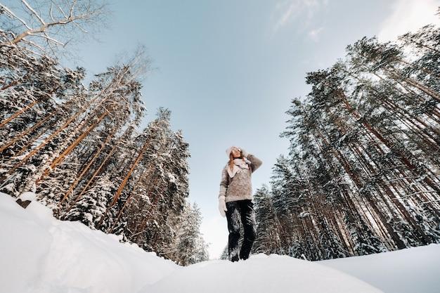 冬のセーターとミトンの女の子は、雪に覆われた背景に立っています。