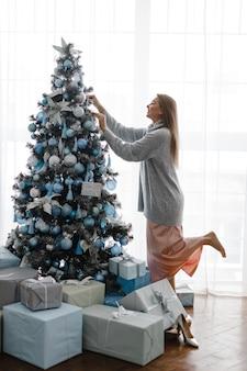 스웨터를 입은 소녀가 창 앞에 서서 크리스마스 트리를 장식합니다. 크리스마스 트리 주변에는 선물이 있습니다. 새해 개념.