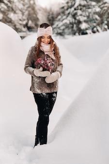 大きな雪の吹きだまりの中に、花束を手にした冬のセーターを着た女の子が立っています。