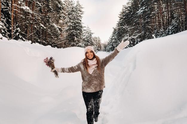 大きな雪の吹きだまりの中に花束を手にした冬のセーターの女の子が立っています