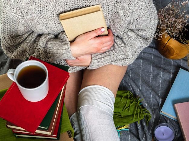 本と毛布の上に座っているセーターの女の子