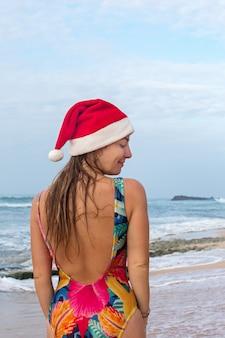 수영복 차림의 소녀와 바다 옆에 서있는 산타 모자