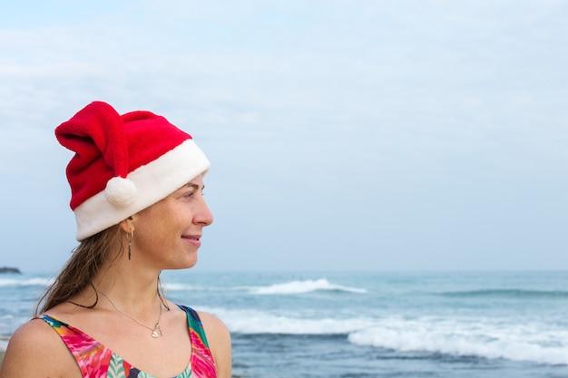 바다에 수영복과 산타 모자에 소녀
