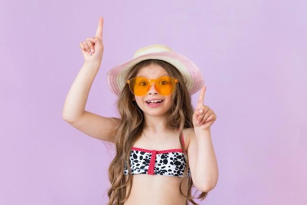 수영복과 선글라스를 쓴 소녀가 손가락을 가리키고 있습니다. 격리 된 배경에.