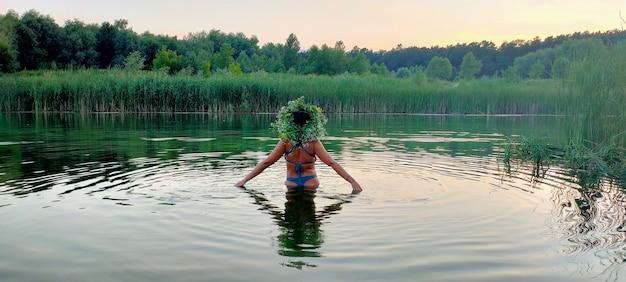 Девушка в купальнике и с букетом цветов на голове стоит в воде