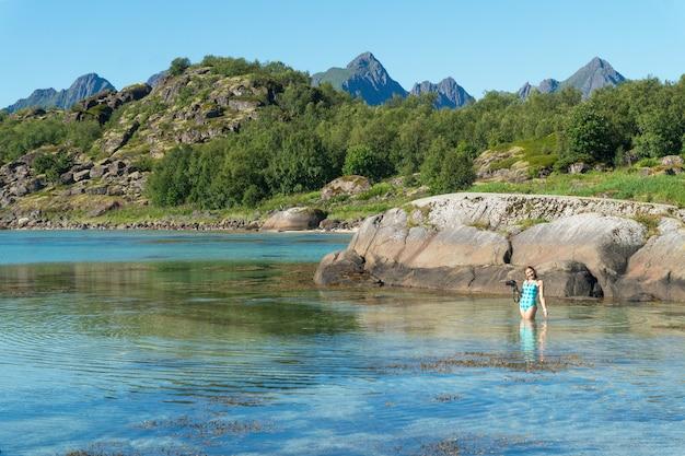 카메라가 있는 수영복을 입은 한 소녀가 노르웨이 로포텐 군도, 아르슈타인 섬, 돌과 푸른 언덕을 배경으로 만의 청록색 투명한 물에 서 있습니다.
