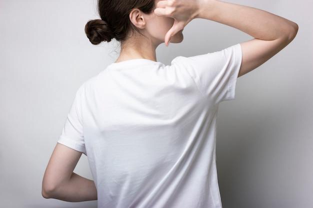 Tシャツを着た女の子が立って手を後ろに向けています。ブランディングの場合は空白。