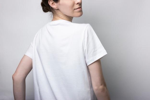 Tシャツを着た女の子が背中と立っています。ブランディングの場合は空白。モノクロモックアップ