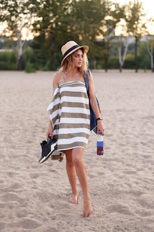 수건에있는 소녀와 밀짚 모자는 그의 손에 서류 가방 물과 신발을 들고 해변에 선다.