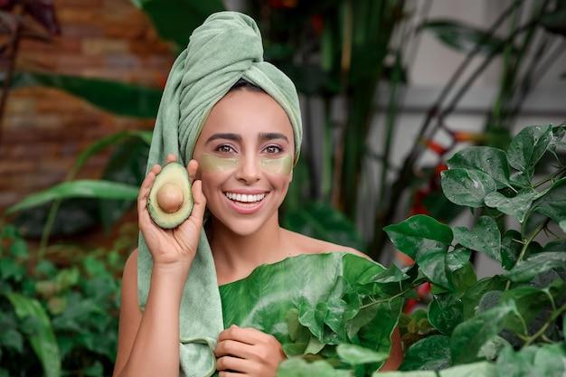 目の下にパッチを置いてポーズをとる彼女の頭の上のタオルの女の子 Premium写真