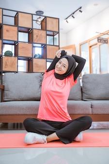 Девушка в спортивном костюме с вуалью улыбается, делая растяжку рук, сидя на полу с ковриком, прежде чем выполнять тренировки в помещении дома