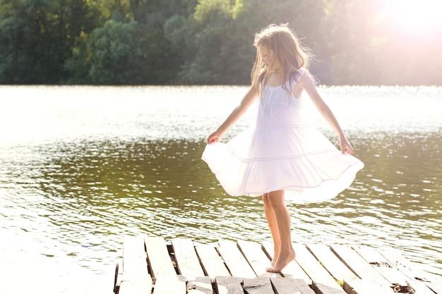 강 근처에서 춤추는 젖은 하얀 드레스를 입은 소녀