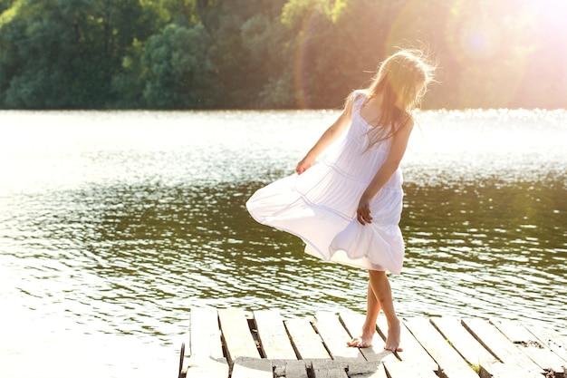 강 근처에서 춤을 추는 젖은 흰 드레스의 소녀