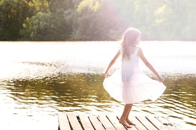 강 부두에서 춤추는 젖은 하얀 드레스를 입은 소녀