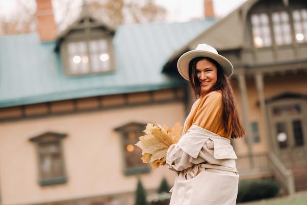 白衣と帽子をかぶった少女が秋の公園で微笑む黄金の秋の女性の肖像