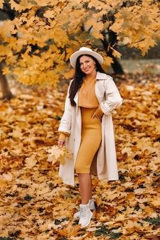 白衣と帽子をかぶった少女が秋の公園で微笑む