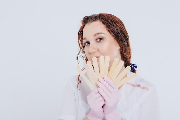 手に木の棒がある白いコートの女の子。医者はワックスの準備をしています。医学概念、医療機器、ヘルスケア、美容業界、脱毛、天然素材