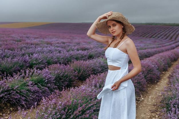 Девушка в белом платье и соломенной шляпе в лавандовом поле