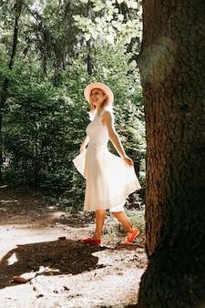 白いドレスと帽子をかぶった女の子が夏の公園や森を歩く