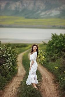 黄色い野の花の花束とエレガントな帽子をかぶった白いドレスを着た女の子