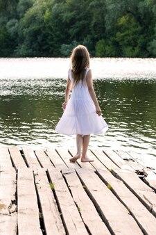 하얀 드레스를 입은 소녀가 강가의 목재 부두에 서 있습니다. 뒤에서보기