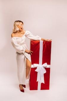 白い背景に巨大な赤い贈り物と白いドレスを着た女の子が微笑む。